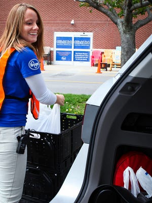Ashley Patton, ClickList manager, takes an order to a Clicklist customer. Kroger employees deliver orders to customers' vehicles.