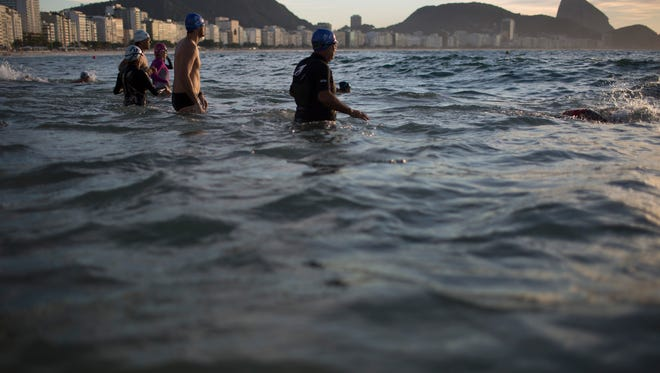 In this July 14, 2015 photo, beachgoers wade into the waters of Copacabana Beach in Rio de Janeiro, Brazil. An Associated Press analysis of water quality found not one water venue safe for swimming or boating in Rio's waters. Over 10,000 athletes from 205 countries are expected to compete in next year's Summer Olympics. Hundreds of them will be sailing in the waters near Marina da Gloria in Guanabara Bay; swimming off Copacabana Beach; and canoeing and rowing on the brackish waters of the Rodrigo de Freitas Lake.