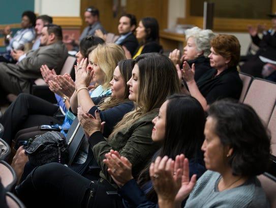 People clap as Mayor Joe McComb speaks about human