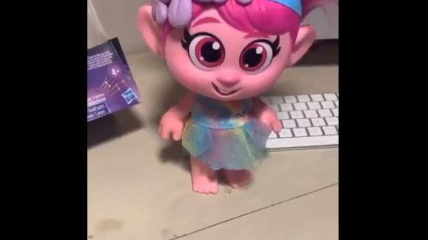 This screenshot shows a DreamWorks Trolls World Tour Giggle and Sing Poppy doll, which Hasbro said will be pulled from stores after concerns were raised about whether the doll grooms children for abuse, due to a sensor between the doll's legs that causes it to giggle when pressed or activated.