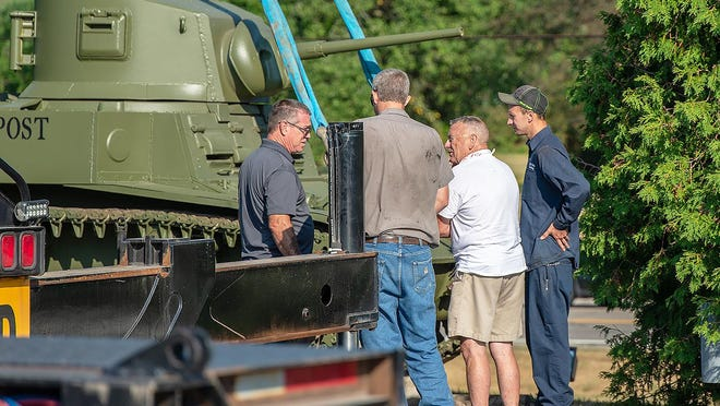 A group including workers from John Ferris Trucking of Bath and leaders of the Steuben County Veterans' Memorial discusses the placement of the newly-restored M3 tank at the memorial site.