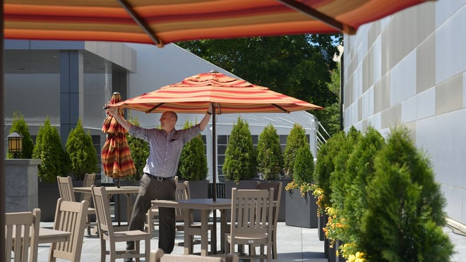 110 Grill General Manager Michael Mills expands the umbrellas along Front Street in preparation of outdoor dining on June 8.