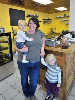 Owner Maggie Christians, center, stands with her daughters, Naomi, 1 and Genevieve, 3, in Navieve Fromagerie, a specialty cheese shop that will open Oct. 5. Christians named the shop by combining the names of her two daughters.
