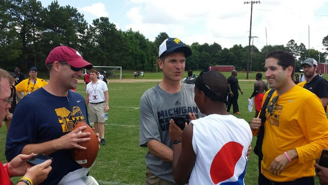 Michigan coach Jim Harbaugh, with Prattville High coach Chad Anderson watching with sunglasses, talks with a fan Friday after the Prattville Elite Football Camp at Prattville High