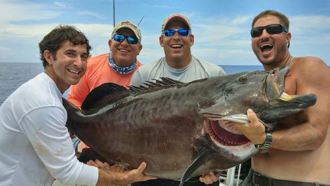 Members of the Sunset Air team show off the 124-plus pound black grouper caught by Alex Newman during the Ronald McDonald House rodeo fishing tournament Saturday in the Gulf of Mexico.