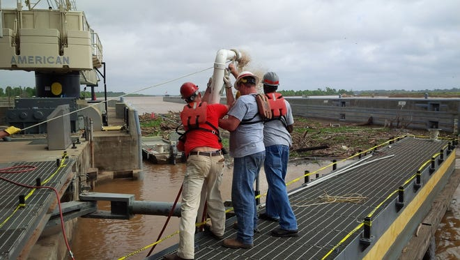 Crews use a suction device to pull sediment out of Lock and Dam No. 5 on Monday.
