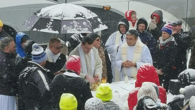 Members of the Sioux Falls Catholic Diocese celebrate Mass alongside the Interstate.