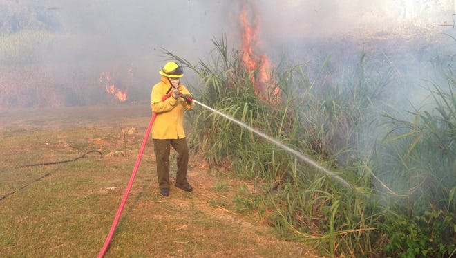 A grass fire blackened the earth and filled the air with smoke in Talofofo on April 11.