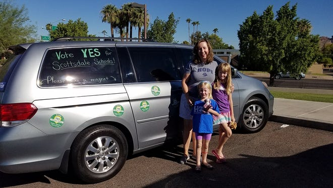 """The disc-shaped magnets have become the signature of the """"Yes to Children"""" citizens' committee working in support of the bond and override proposals for the Scottsdale Unified School District. Laura Mitchell and her children, Holly and Kelly, show their support by turning their van into a mobile billboard."""