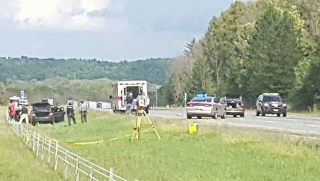 Law enforcement approaches a vehicle in a stand-off that shut down three exits of I-71 near Mansfield Sunday. A suspect in a shooting at a Delaware rest stop reportedly was involved.