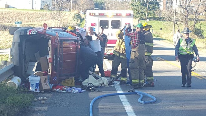 Emergency responders work to pull two people from a Ford Escape after a crash at Ohio 60 and County Road 1894 just north of Hayesville on Thursday.