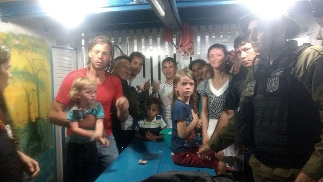 A handout picture provided by ASCOM/SEGUP,shows US citizens Adam Harris Harteau, his wife, Emily Faith Harteau and their two children with Brazilian security personnel.