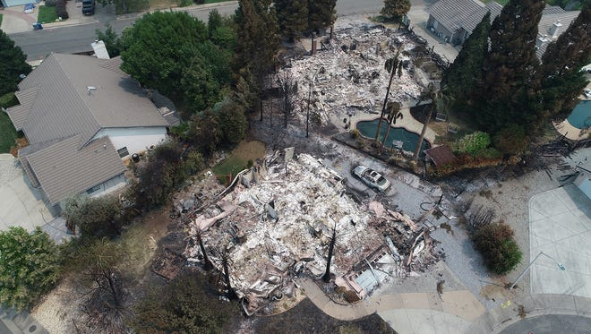Homes in the River Ridge Park subdivision show the damage from the Carr Fire Wednesday August 1, 2018 in Redding, CA. These homes on Diamond Bar Ct. are completely destroyed, foreground, while most on River Ridge Road are fine.
