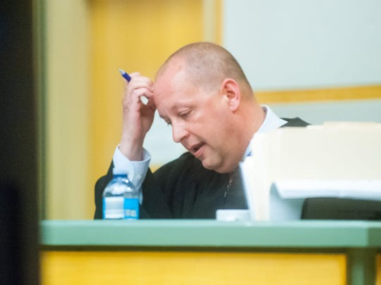 Judge Robert G. Malestein looks over evidence during