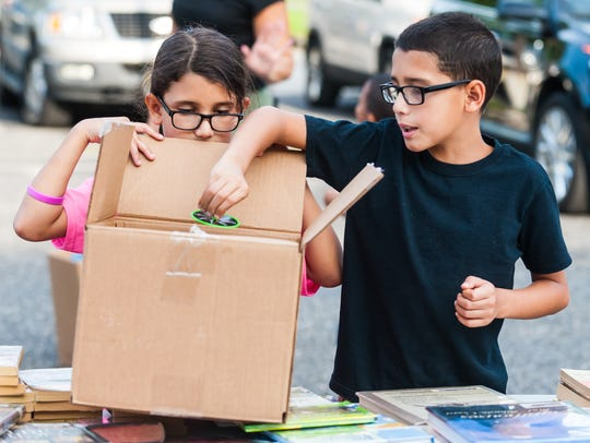 Makayla, 8, and Michael Smith, 9, load up a box with