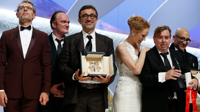 "Director Nuri Bilge Ceylan, center, poses with the Palme d'Or award for the film ""Winter Sleep"" and Actor Timothy Spall, second right, poses with his award for Best Actor for his role in the film ""Mr. Turner"" during the awards ceremony for the 67th international film festival, Cannes, southern France, Saturday, May 24, 2014. At third right is presenter actress Uma Thurman and at second left is director and presenter Quentin Tarantino."