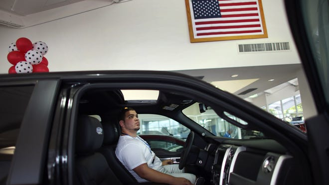 Roger Rodriguez looks at a F-150 pickup on the showroom floor at a Ford AutoNation car dealership in North Miami, Fla., on Sept. 4.