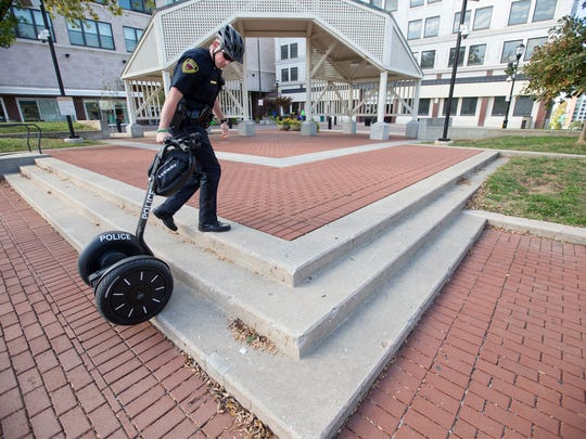 Officer Kyle Campbell pulls a Segway up the steps in Park Central Square on Thursday, Oct. 20, 2016.