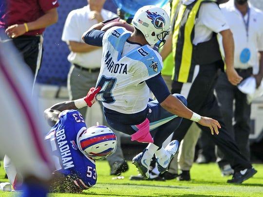 Bills outside linebacker Nigel Bradham pulls down Titans quarterback Marcus Mariota during the fourth quarter at Nissan Stadium.