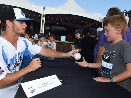 Hudson Valley Renegade Jim Haley hands back Justin Quinn of Millbrook's ball during during an autograph session prior to the start of the New York Penn League All Star Game at Dutchess Stadium on Tuesday.