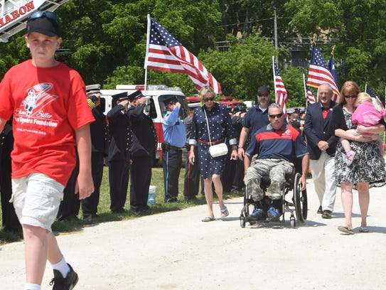 Former Army Staff Sgt. Stephen Valyou, right, travels