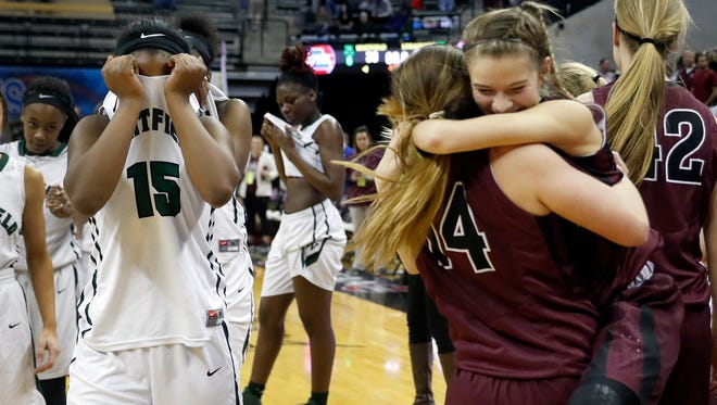 Whitfield's Nia Griffin, left, hides her face with her jersey as Mica Chadwell, center, and teammate Kyndall Compton celebrate after Strafford's 80-39 victory in the Missouri Class 3 girls high school championship basketball game Saturday, March 11, 2017, in Columbia, Mo. Strafford won 80-39.