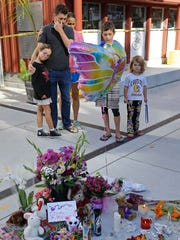 A family pays their respects beside a memorial for