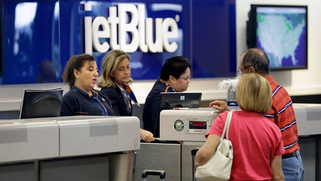 JetBlue Airways ticket agents assist passengers Oct. 26, 2016,  at the ticket counter at the Tampa International Airport in Tampa, Fla.