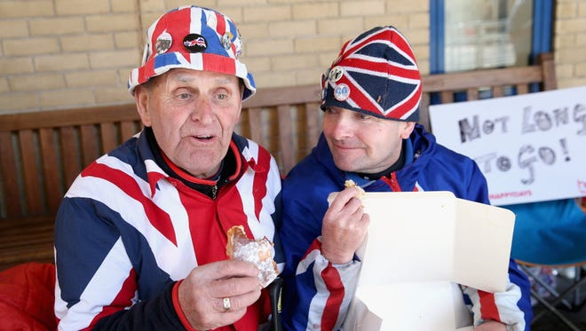 Royalists Terry Hutt and John Loughrey enjoy the last of some pastries allegedly delivered to them by Prince William, Duke of Cambridge and Catherine, Duchess of Cambridge as they wait at the Lindo wing for the Duchess to go into labor at St Mary's Hospital on April 27, 2015, in London.
