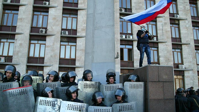 A pro-Russian masked activist waves a Russian national flag above Ukrainian police at the regional administration building in Donetsk, Ukraine, on April 6.