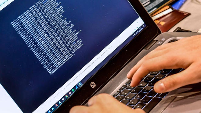In this file photo taken on January 23, 2018 a person works at a computer during the 10th International Cybersecurity Forum in Lille, France.