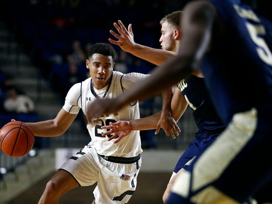 Navy guard Shawn Anderson drives to the basket against Pittsburgh defenders during the second half of an NCAA college basketball game at the Veterans Classic tournament in Annapolis, Md., Friday, Nov. 10, 2017. Navy won 71-62. (AP Photo/Patrick Semansky)
