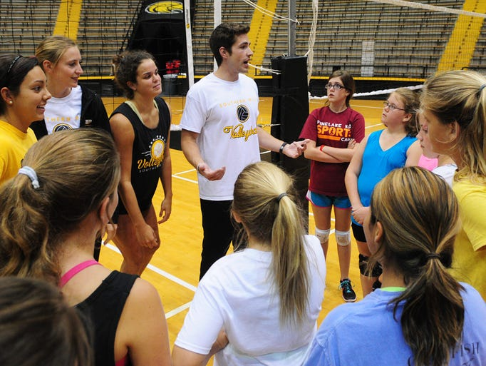 Southern Miss assistant volleyball coach David Brown, center, talks with girls participating in the All Skills Volleyball Camp at Reed Green Coliseum.