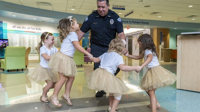 In this photo provided by Johns Hopkins All Children's Hospital, security guard David Dean dances with McKinley Moore, Avalynn Luciano, Lauren Glynn and Chloe Grimes at the hospital in St. Petersburg, Florida, in 2018. The girls, who were diagnosed with cancer in 2016 and became fast friends while undergoing treatment, reunite every year.