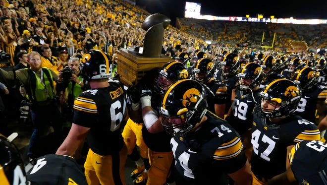 Members of the Iowa Hawkeyes football team carry the Cy-Hawk trophy off the field after a 42-3 win over Iowa State on Saturday, Sept. 10, 2016, at Kinnick Stadium in Iowa City.