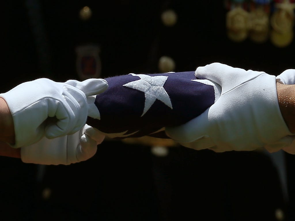 Members of a U.S. Army burial team fold the American flag that covered the casket containing the remains of World War II U.S Army Air Force 2nd Lt. Alvin Beethe, of Elk Creek, Neb., during Beethe's full military honors burial service at Arlington Nat