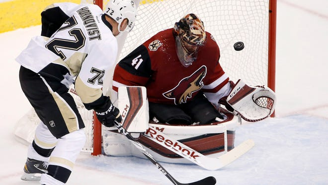 Arizona Coyotes goalie Mike Smith makes a save on a shot by the Pittsburgh Penguins' Patric Hornqvist during the first period of an NHL hockey game on Saturday, Oct. 10, 2015, in Glendale.