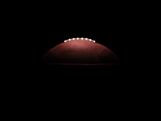 American football ball on black background