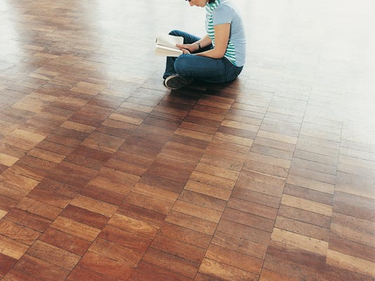 Female University Student Sitting Cross-legged on a Wooden Floor Reading a Book