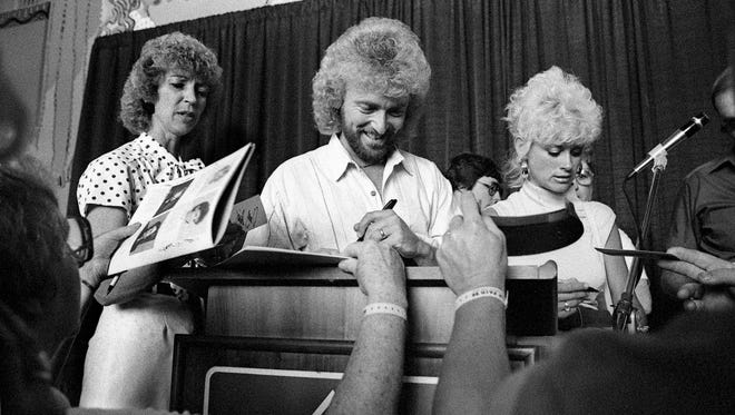Country stars Keith Whitley, center, and wife Lorrie Morgan, right, sign autographs for fans after the induction of Morgan's late father, George Morgan, into the Country Music Hall of Fame and Museum's Walkway of Stars' Fan Fair event June 6, 1988.