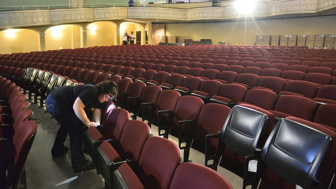 Sarah Lemanski and other crew members work to install the 806 new American Seating seats Thursday afternoon at the Paramount Theatre in downtown St. Cloud.