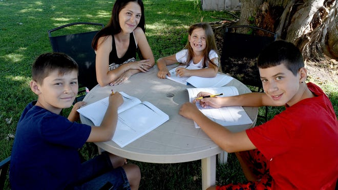 Casey Gibbons helps her children Jace, 10, Sophia, 6, and Kaiden, 12, with homework at their home in Luna Pier. The children are enrolled in virtual school.