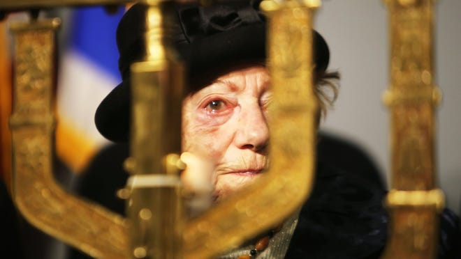 Hanna Ungar, 90, of Oak Park, a Holocaust survivor from Latvia, participates in a candle-lighting ceremony with her family as a part of the Holocaust Day of Remembrance program Sunday in Farmington Hills.