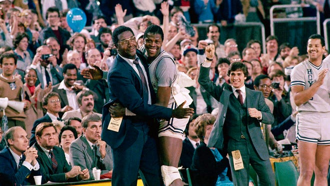 Georgetown coach John Thompson, left, gives a happy pat to Patrick Ewing after Georgetown defeated Houston for the 1984 NCAA title.