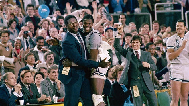 Georgetown head coach John Thompson, left, gives a happy pat to the most valuable player Patrick Ewing, after Georgetown defeated Houston 84-75 on April 2, 1984 in Seattle.