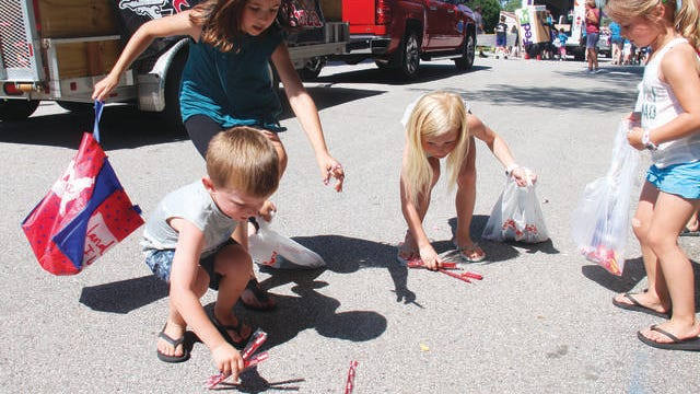From left, Kyson Quam, Annabelle McNertney, Kenley Quam and McKinley Dana pick up candy during the 2019 Governors Days parade. The 2021 parade returns on Saturday, June 12.