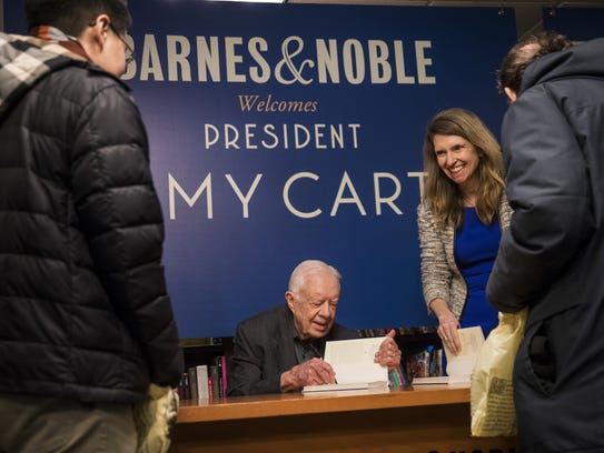 Former U.S. President Jimmy Carter signs a copy of his new book 'Faith: A Journey For All' at an event at Barnes & Noble bookstore in New York City, March 26, 2018. Carter, 93, has been a prolific author since leaving office in 1981, publishing dozens of books.