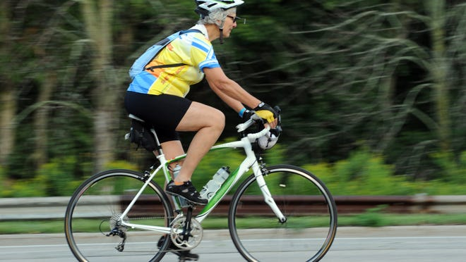A bicyclist rides on the streets of Lansing as DALMAC riders began their journey Wednesday morning after leaving East Lansing.