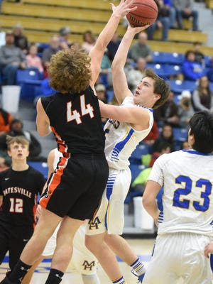 Mountain Home's Colton Peters lofts a shot over Batesville's JP Morgan during a recent game at The Hangar.
