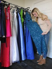 Addison Lobaugh displays some of the gowns and prom